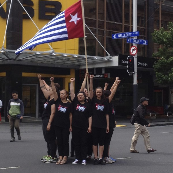 Māori and Pacific women raising fists and the Morning Star to support a free and independent West Papua